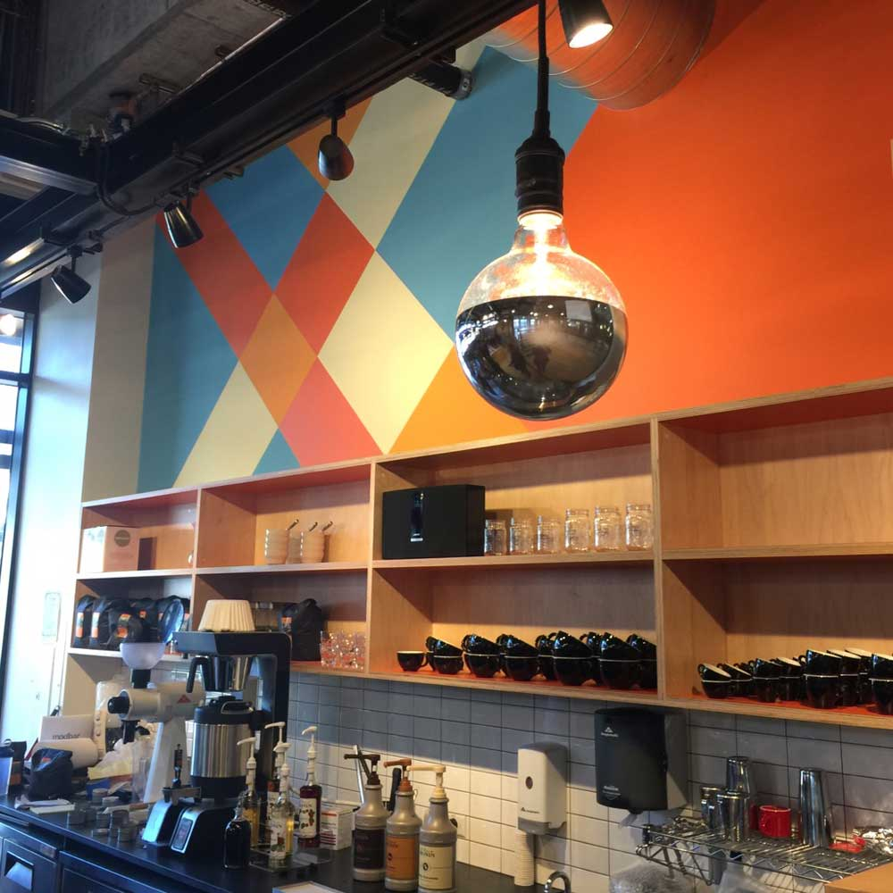 Geometric Colorful Mural and Chrome lighting provide warmth and energy at Caffe Ladro 400 Fairview Seattle