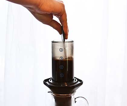 Aeropress with coffee and water and hand stirring contents