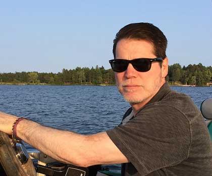 Ladro Profiles Bob Ohly, Partner and CFO at Caffe Ladro/Ladro Roasting driving a pontoon in Minnesota