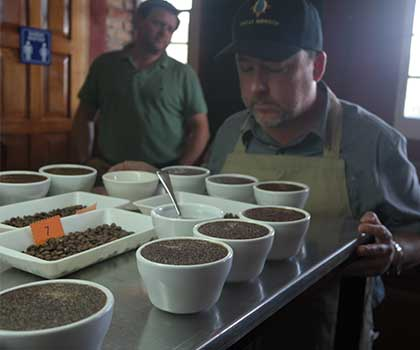 Jack Kelly, head coffee buyer for Ladro Roasting, prepares to score a table full of coffee samples using the coffee cupping method